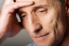 Depressed mature man touching his head. Worried mature man touching his head stock image