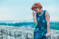 Depressed mature woman feeling alone outside Royalty Free Stock Images