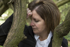 Depressed middle age woman in forest leaning on a tree royalty free stock photography