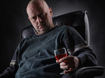 Depressed middle aged alcoholic and wine glass Royalty Free Stock Photos