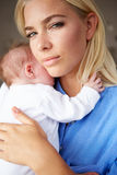 Depressed Mother Cuddling Newborn Baby Stock Image
