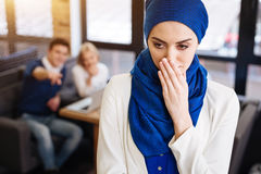 Depressed muslim woman feeling humiliated. In need of social security. Depressed cheerless muslim women standing in the cafe while her colleagues abusing her and Royalty Free Stock Photos