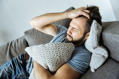 Depressed nice man suffering from headache. Health problems. Depressed nice young man lying on the sofa and holding his forehead while suffering from a headache Stock Images