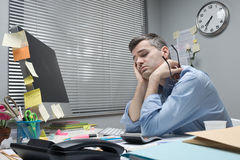 Depressed office worker at his desk Stock Photos