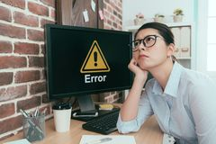 Depressed office worker lady sitting in front of error computer. Daydreaming thinking working solution and waiting for help stock images