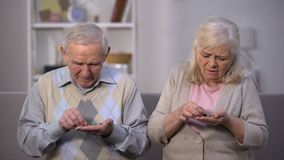 Depressed old couple counting coins in open palm, no money for living, poverty stock video footage