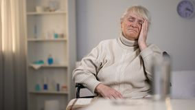 Depressed old lady suffering from head ache looking at pills, medical center. Stock footage stock video