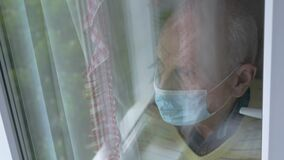 Depressed old man in mask reflection in window overhead view