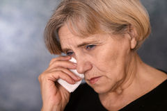 Depressed old woman. On a gray background Royalty Free Stock Photos