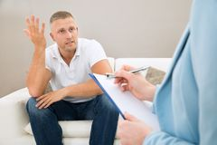 Depressed patient in front of psychiatrist Royalty Free Stock Photography