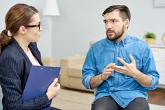 Having Face to Face Problem Discussion. Depressed patient wearing denim shirt having face to face problem discussion with highly professional psychologist after Stock Photography