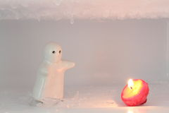 The depressed person   want  to embrace candle   in the  ice. The depressed person and dark candle   in the snow and ice Royalty Free Stock Photo