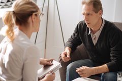 Depressed pessimistic man sharing his problems. Psychologist session. Depressed pessimistic pleasant men looking at his therapist and sharing his problems with Stock Photo