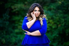 Depressed plus size fashion model in blue dress outdoors, beauty woman with professional makeup and hairstyle Stock Image