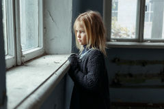 Depressed poot girl standing near window. Hopeless life. Close up of depressed poor little girl standing near window and looking aside while feeling miserable Stock Photo