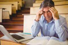 Depressed professor sitting with notes and laptop Stock Images