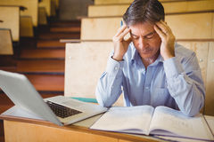 Depressed professor sitting with notes and laptop royalty free stock photography