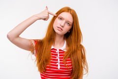 Depressed redhead young woman with finger to temple like gun Royalty Free Stock Images