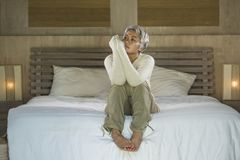 Dramatic lifestyle home portrait of attractive sad and lost middle aged woman with grey hair sitting on bed feeling frustrated. Depressed 40s - 50s mature female stock image