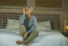 Dramatic lifestyle home portrait of attractive sad and lost middle aged woman with grey hair sitting on bed feeling frustrated. Depressed 40s - 50s mature female royalty free stock images