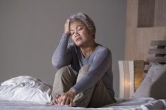 Dramatic lifestyle home portrait of attractive sad and lost middle aged woman with grey hair sitting on bed feeling frustrated. Depressed 40s - 50s mature female royalty free stock photos