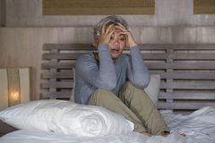 Dramatic lifestyle home portrait of attractive sad and lost middle aged woman with grey hair sitting on bed feeling frustrated. Depressed 40s - 50s mature female royalty free stock photography