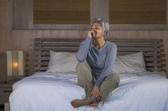 Dramatic lifestyle home portrait of attractive sad and lost middle aged woman with grey hair sitting on bed feeling frustrated. Depressed 40s - 50s mature female royalty free stock image