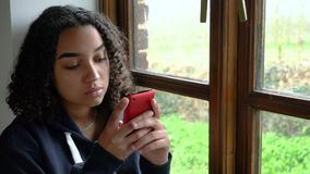 African American girl teenager depressed sitting by a window using her mobile cell phone or smartphone. Depressed sad beautiful mixed race African American girl stock video