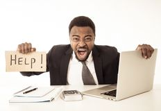 Depressed sad and frustrated young businessman holding a help sign in stress at workplace stock images