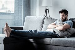 Depressed sad man holding a cushion. State of loneliness. Depressed nice sad man sitting on the sofa and holding a cushion while suffering from loneliness stock image