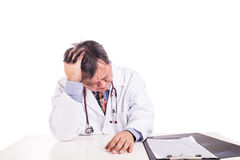 Depressed sad matured Asian doctor seated behind desk. On white background Royalty Free Stock Photos
