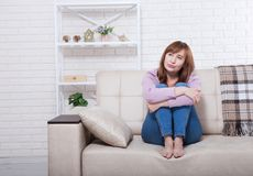 Depressed and sad middle aged woman sitting with clamped knees on bed, coach, sofa at home. Copy space and mock up. stock images
