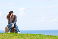 Depressed, sad and upset young woman. A strong image of a depressed and upset young woman sitting outside with her head in her hands royalty free stock image