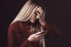 Depressed sad woman holding phone isolated.