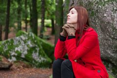 Depressed and sad young woman feeling depression sitting on forest, looking up with melancholic thinking royalty free stock photo