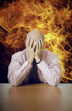 Depressed senior businessman sitting at desk with fire in background Stock Photography