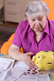 Depressed senior citizen looking for piggy bank Royalty Free Stock Image