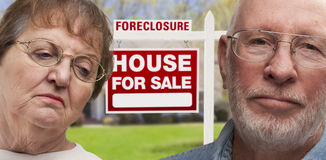 Depressed Senior Couple in Front of Foreclosure Sign and House Stock Photos