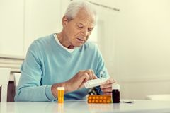Depressed senior gentleman taking pills. Sad mood. Low angle shot of an upset elderly man sitting at a table and holding a weekly organizer while taking his stock images