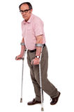 Depressed senior male with two crutches. Depressed senior male standing with two crutches isolated over white Stock Images