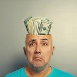 Depressed senior man with money. Depressed senior man having open head with money over grey background Stock Photo