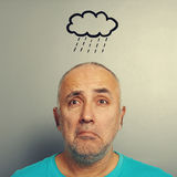 Depressed senior man. Portrait of depressed senior man with drawing storm cloud over grey background Stock Photography