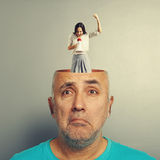 Depressed senior man and screaming woman. Depressed senior men with open head. young screaming women standing in the head, looking at the men and screaming with Royalty Free Stock Photography