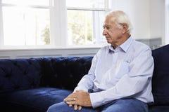 Depressed Senior Man Sitting On Sofa At Home Stock Photo