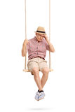 Depressed senior man sitting on a swing. Vertical shot of a depressed senior man sitting on a swing and remembering something isolated on white background Stock Images