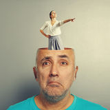 Depressed senior man and smiley woman. Depressed senior men with open head. young smiley women standing in the head and pointing at something. photo over grey Royalty Free Stock Photography