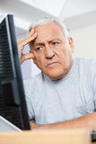 Depressed Senior Student Looking At Computer. Depressed senior male student looking at computer while sitting in classroom Stock Photo