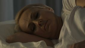 Depressed senior woman lying in bed and thinking about family problems, insomnia. Stock footage stock video footage
