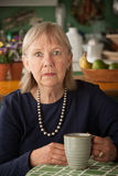 Depressed senior woman with mug Stock Photography