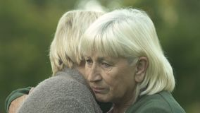 Depressed senior women hugging each other, friendship support, family problem